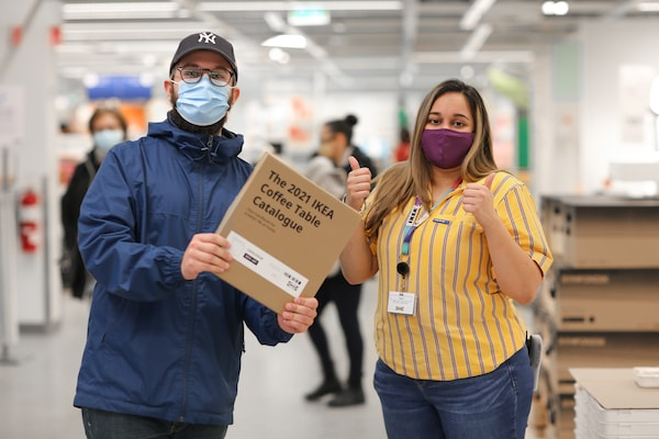 A co-worker giving the thumbs up to an IKEA Family member holding their IKEA Coffee Table Catalogue