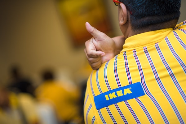 A co-worker in an IKEA uniform giving a thumbs up over his shoulder with his back turned.