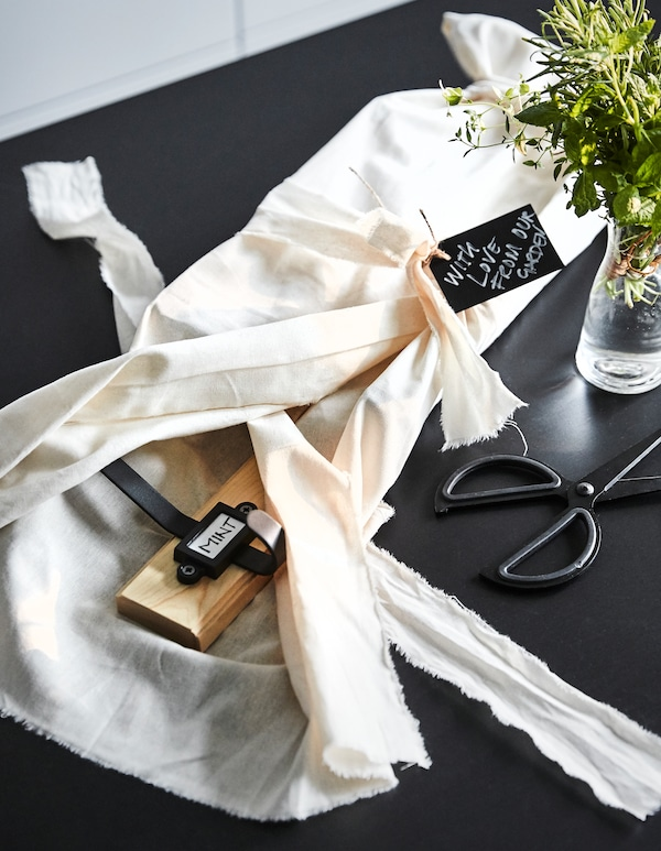 A coat rack, wrapped partially in linen and with a gift tag, on a table with scissors and herbs in a glass vase.