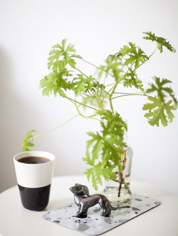 A coffee cup, branch and dog ornament displayed together.