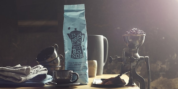 A coffee packet, mugs and a traditional coffee grinder filled with coffee beans.