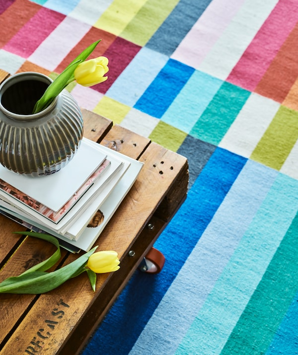 A coffee table made from a repurposed palette and red castors on a colourful stripy rug, magazines and a grey vase on top.
