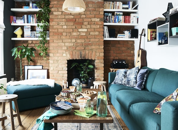 A coffee table set with food in a living room with a green sofa and red brick wall.