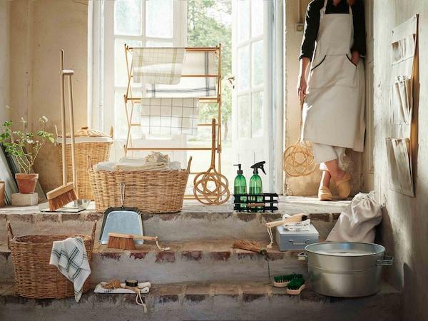 A colección de produtos BORSTAD diante dunha porta pola que entra o sol; detrás hai unha muller que suxeita o atizador de alfombras.