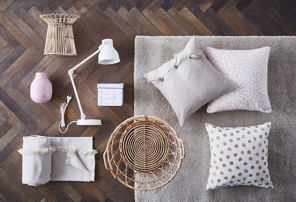 A collage of cushions, textiles, a basket and a lamp on a wooden floor.