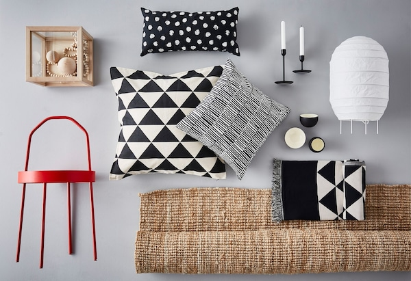 A collage of IKEA products including a red table, a rug and several black and white cushions.