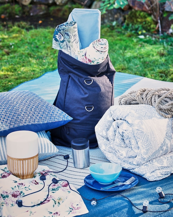 A collection cushions, blankets and lamps laid out on a picnic blanket.