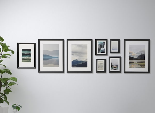A collection of artwork in black frames on a white wall.