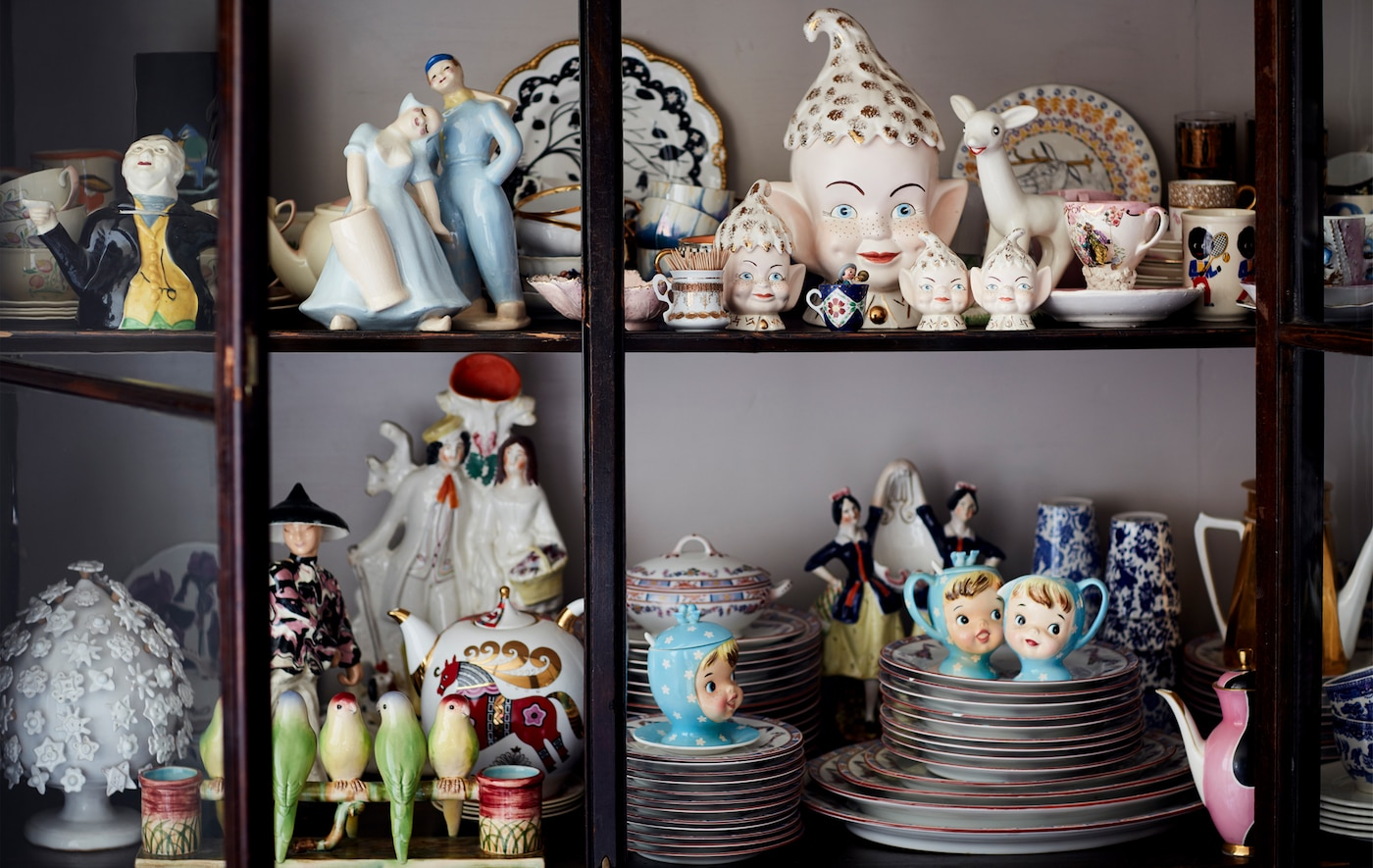 A collection of china ornaments in a glass-fronted cabinet.