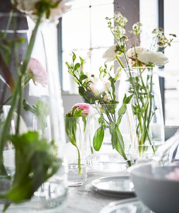 A collection of clear glass vases with flower arrangements on a dining room table.