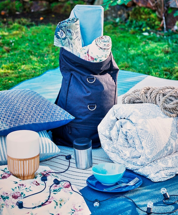 A collection of cushions, blankets and lamps placed on a picnic blanket.