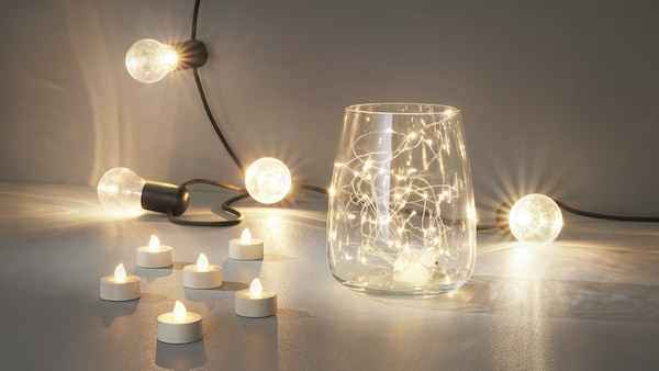 A collection of decorative lighting, including LED tealights and string lights.