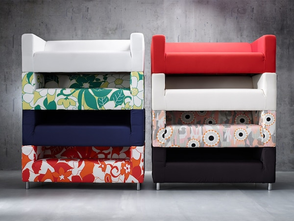 A collection of eight stacked IKEA KLIPPAN sofas with removable covers, shown in different colours and patterns.