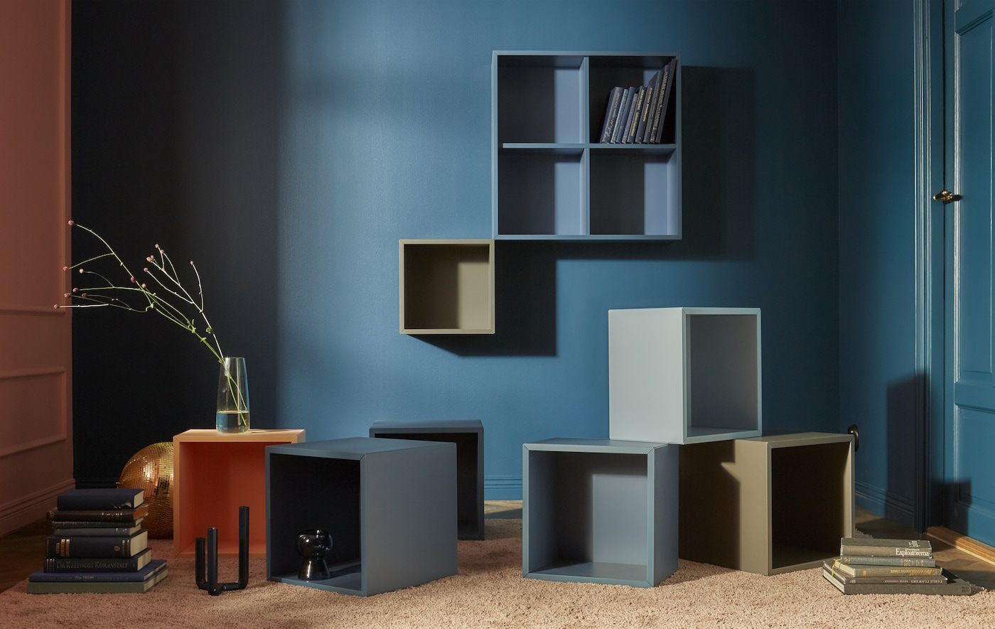 A collection of EKET open cabinets mounted to a dark blue wall and strewn across the floor in blue, brown, and grey colours.