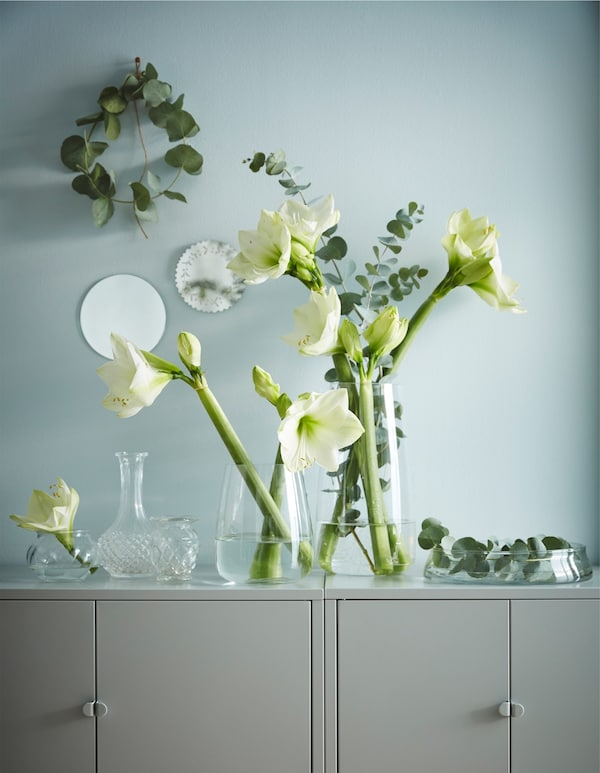 A collection of glass vases filled with white flowers and greenery on a cabinet top.