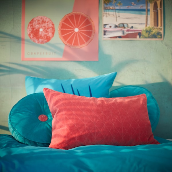 A collection of GRACIÖS cushion cover, cushions and pillowcase in turquoise and pink tones placed on a bed.