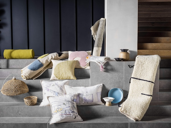 A collection of LOKALT products including pillows with an illustrated city, rugs, and a weaved lamp shade.