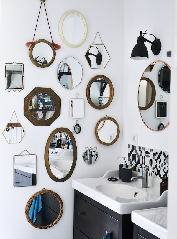 A collection of mirrors in different sizes and shapes mounted on one side of a white bathroom wall.