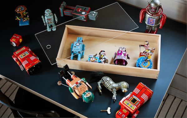 A collection of old robot toys on a table top with an open SAMMANHANG display box.