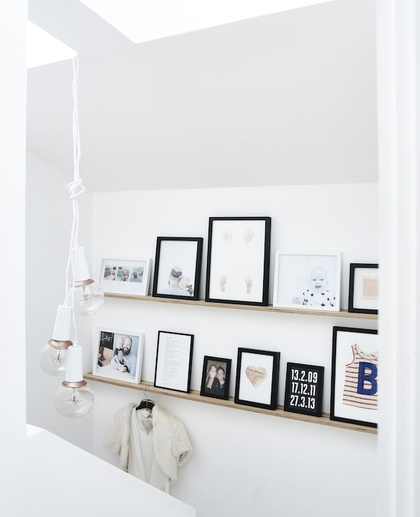 A collection of picture frames in different sizes placed on two mounted picture ledges at different heights.