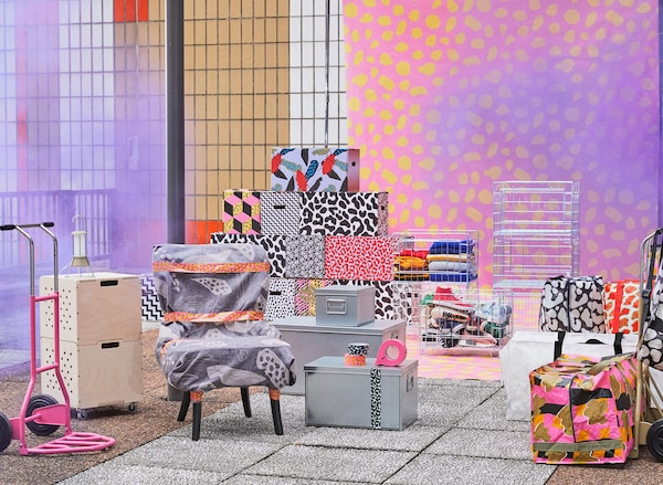 A collection of products from the OMBYTE collection including a dolly, patterned moving boxes, and various bags.