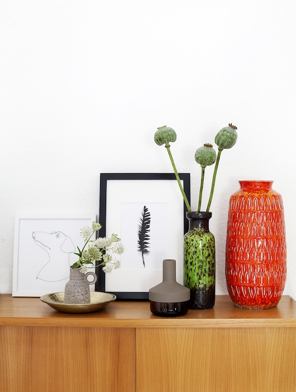 A collection of vases and pictures on top of a cabinet.