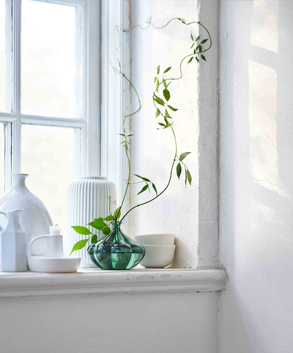 A collection of white ceramic pots sit on a windowsill with a green glass vase at their centre.