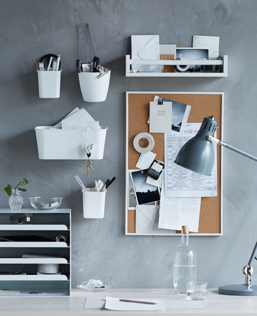 A college dorm room organizing idea showing a desk with wall organizers and a corkboard for messages.