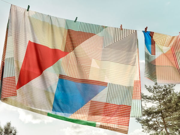 A colorful blanket with blue and red triangles and geometric shapes hanging on a clothes line outside.