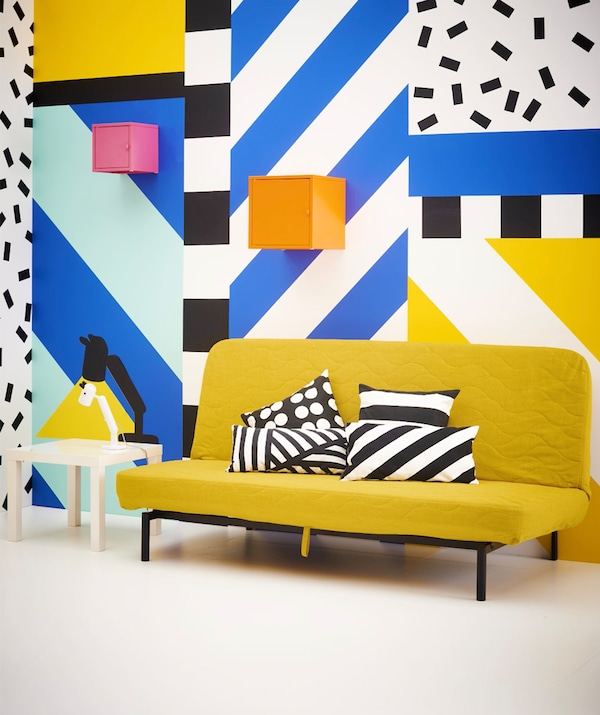 A colorful graphic print room with a yellow sofa bed and pink and orange storage cubes on the wall.