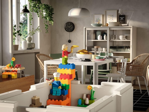 A colorful LEGO brick tower with two LEGO characters inside an open white storage box inside a dining room.