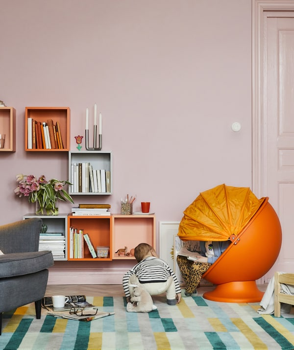 A colorful living room with a kids' orange egg chair and two children reading and playing.