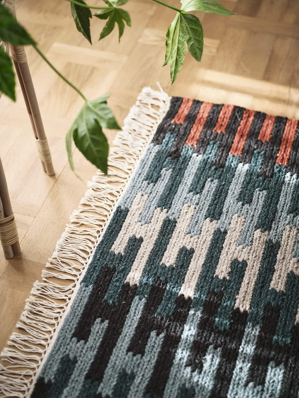 A colorful patterened rug on top of a wooden floor, linking to the rugs page