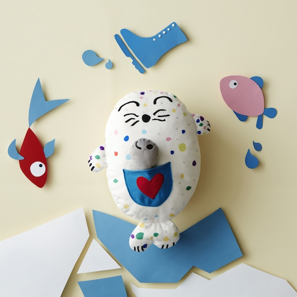 A colorful seal soft toy in a paper cut-out Arctic scene.
