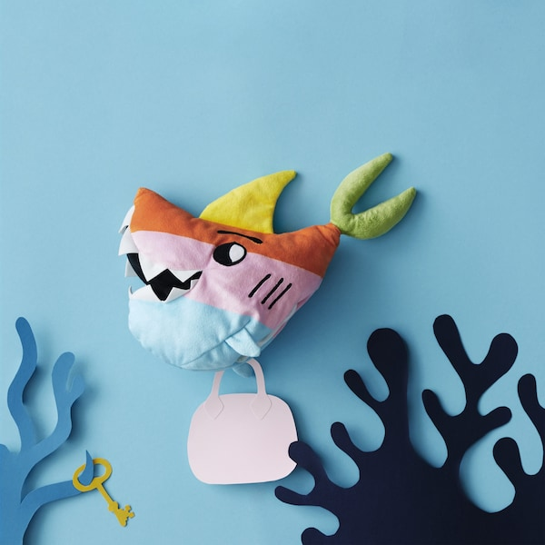 A colorful shark soft toy in a paper cut-out underwater scene.