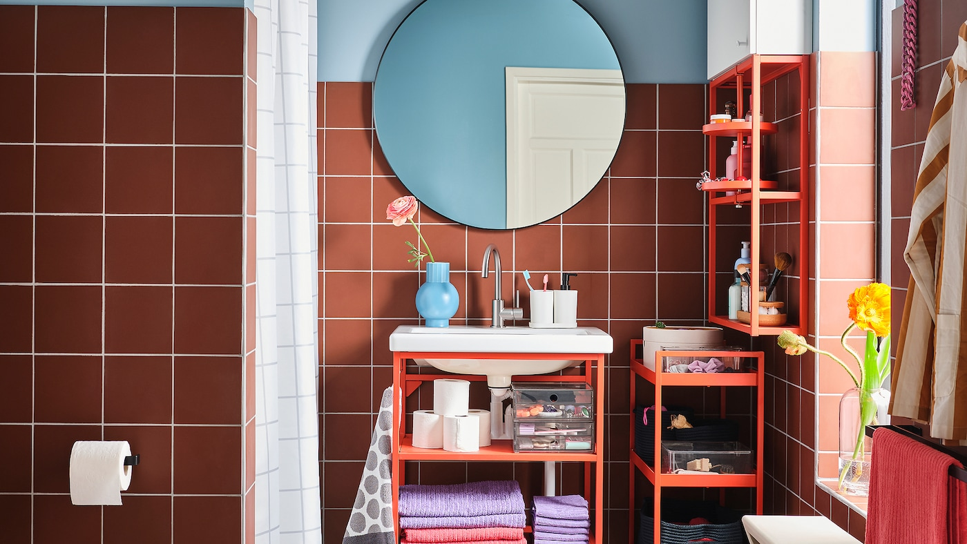 A colourful bathroom with a wash-basin unit, shelf and trolley in red-orange steel and a round mirror.
