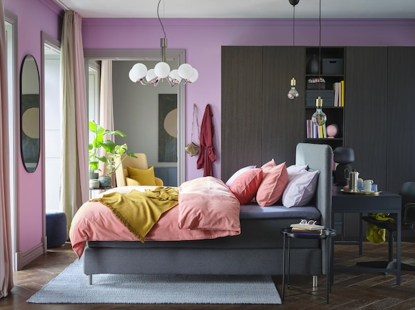 A colourful bedroom with lilac walls, light brown-red bed linen, a yellow throw, a black-brown wardrobe and a grey divan bed.