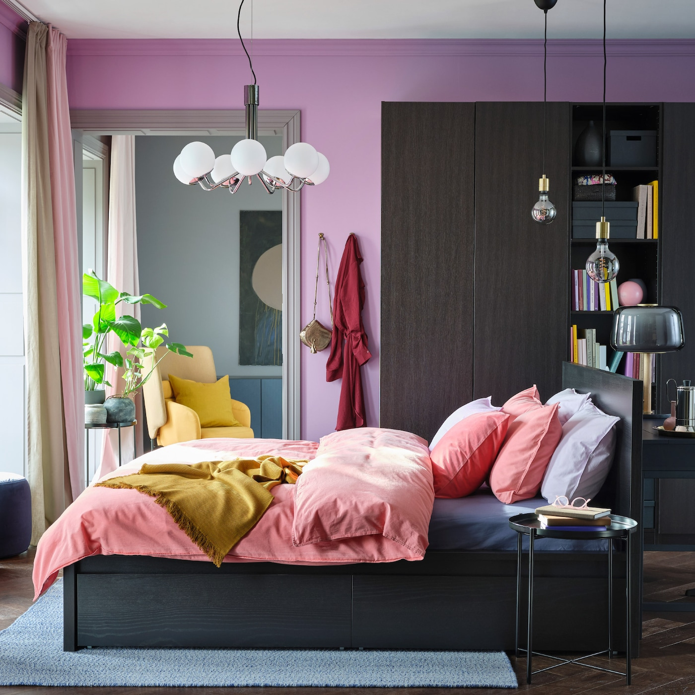A colourful bedroom with lilac walls, light brown-red bed linen, a yellow throw and a wardrobe and bed frame in black-brown.