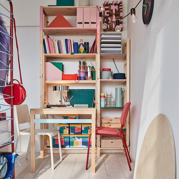 A colourful bedroom work/dining area with a foldable table in pine that's paired with red and white chairs.