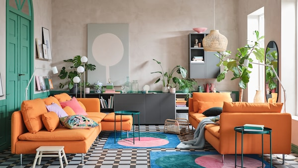 A colourful living room with a sofa and a chaise longue in orange, bold print rugs and green tray tables.