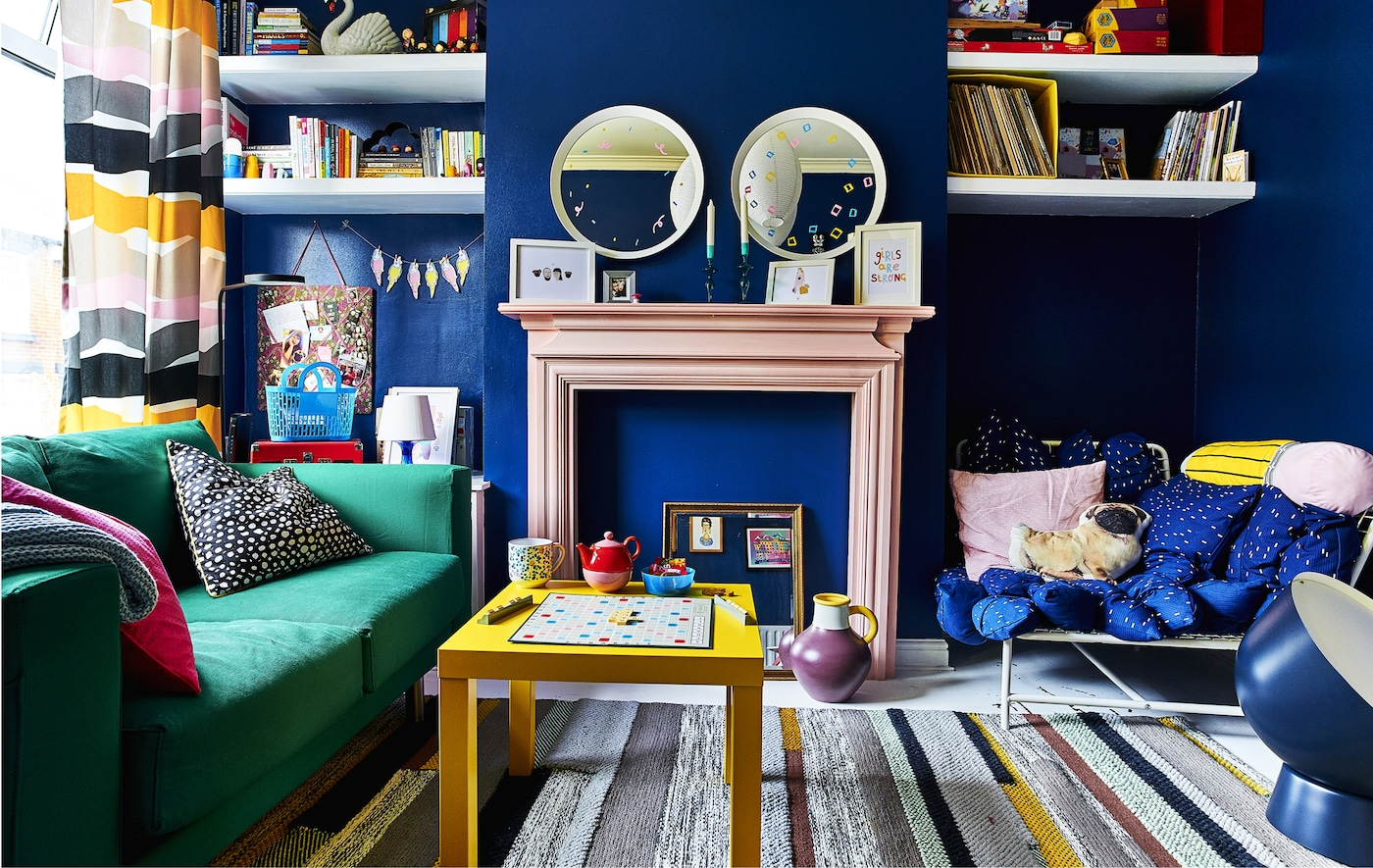 A colourful living room with green sofa and yellow coffee table in front of a pink fireplace mantel against navy blue walls.