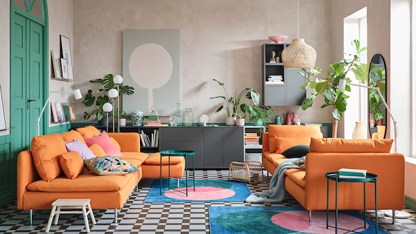 A colourful living room with orange sofas and a rainbow of textile accents.