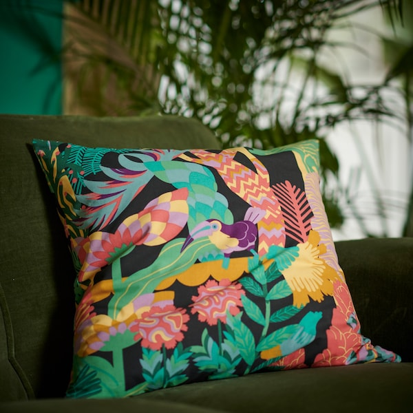 A colourful NÄBBFLY cushion cover featuring a tropical bird among lush greenery and plants placed in a green velvet sofa.