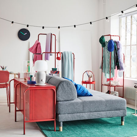 A colourful one-bedroom-apartment with a grey sofa bed, two green rugs and a red chest of drawers.