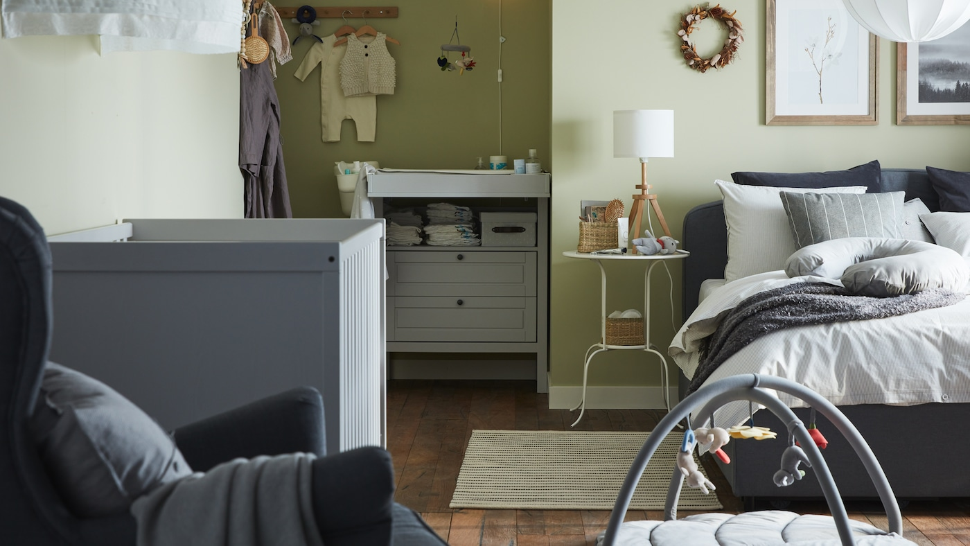 A combined bedroom and baby room with a gray upholstered bed, grey crib, grey changing table/chest of drawers, green walls.