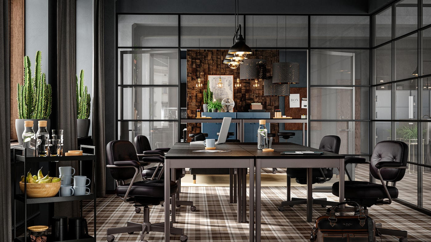 A conference room with dark furniture, glass walls, brown checkered floor, leather seats and cacti by the window.