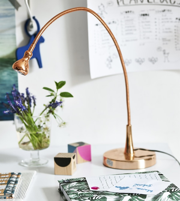 A copper lamp, flowers and stationery on a desk.