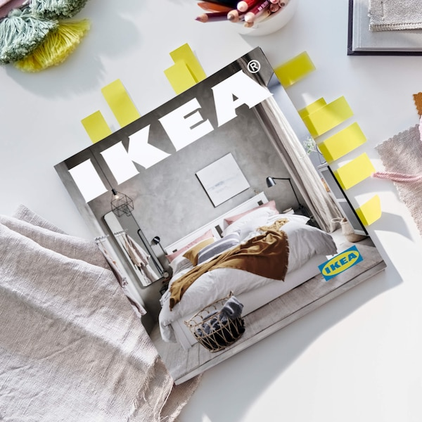 A copy of the 2021 IKEA Catalog on a desk with fabric and scissors