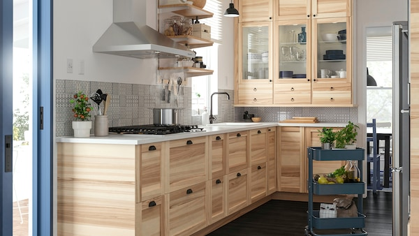 A corner kitchen with traditional natural ash and glass doors and ash cabinets with black cup handles and a dark floor.
