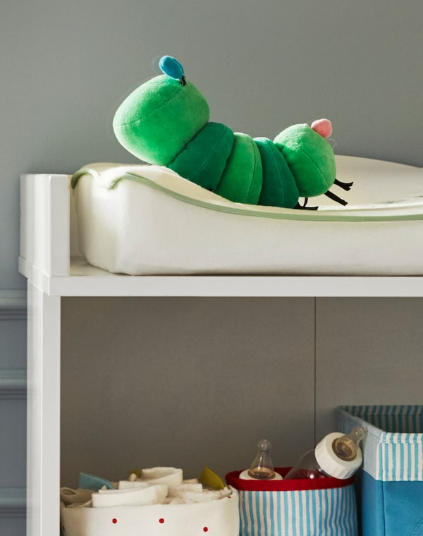 A corner of a baby changing mat with KLAPPA caterpillar soft toy on it and baby milk bottles and cloths in baskets on the shelf below.